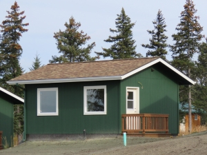 Front view of Peggy's Cabin, a green cabin with white trim.