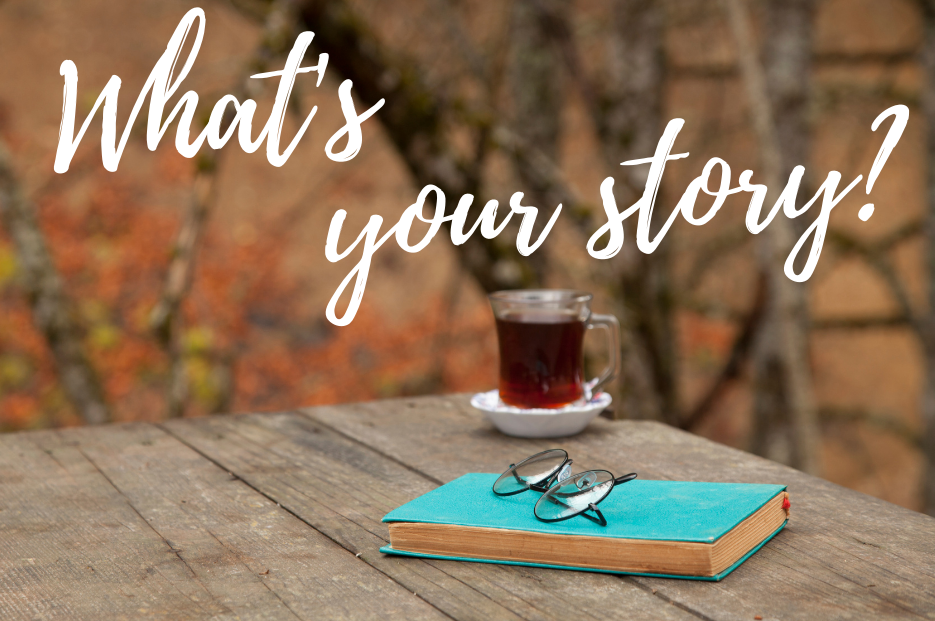 "A cup of tea and a book on an autumn picnic table with the heading ""What's Your Story?"""